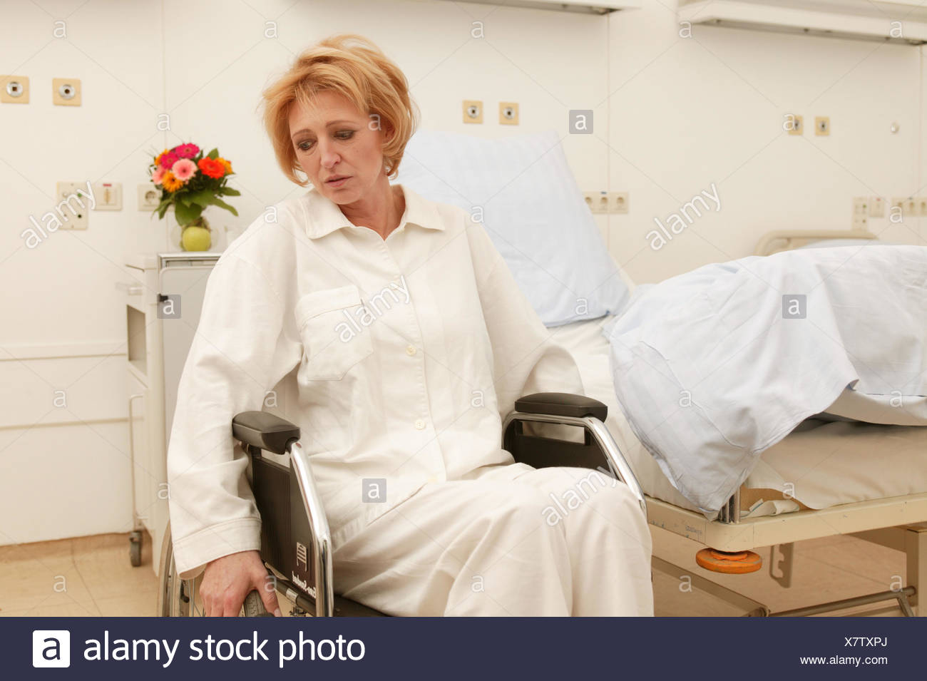 Wards, patient, invalid, wheel chair, sit, suffer sadly, Ti7, medicine, hospital, clinic, hospital, ward, bed, disease, hospitalisation, convalescense, health, woman, 40-50 years, invalid, feet, impediment, hemiplegia, destiny, grief, worries facial play, emotion, view lowered, ailment, - Stock Image