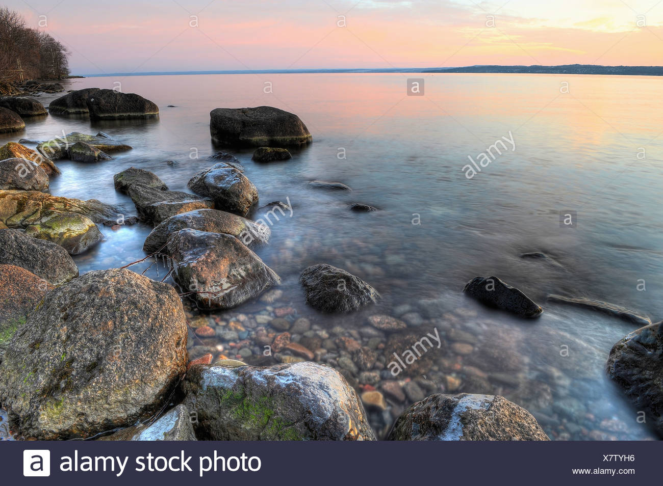 Rock by water's edge - Stock Image