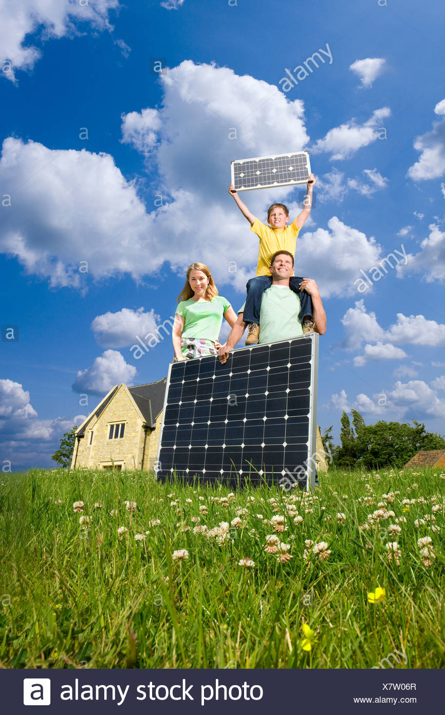 Happy family standing in green field holding solar panels - Stock Image