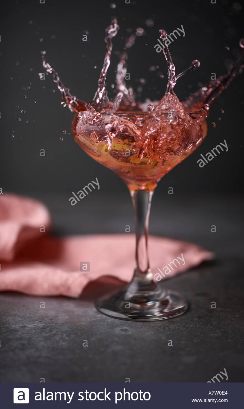 A rich pink cocktail splash on metal surface with pink linen - Stock Image