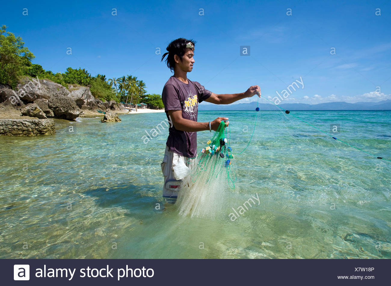 Philippine fisherman catching small bait fish with a net, White Beach, Moalboal, Cebu, Philippines, Indo-Pacific region, Asia - Stock Image