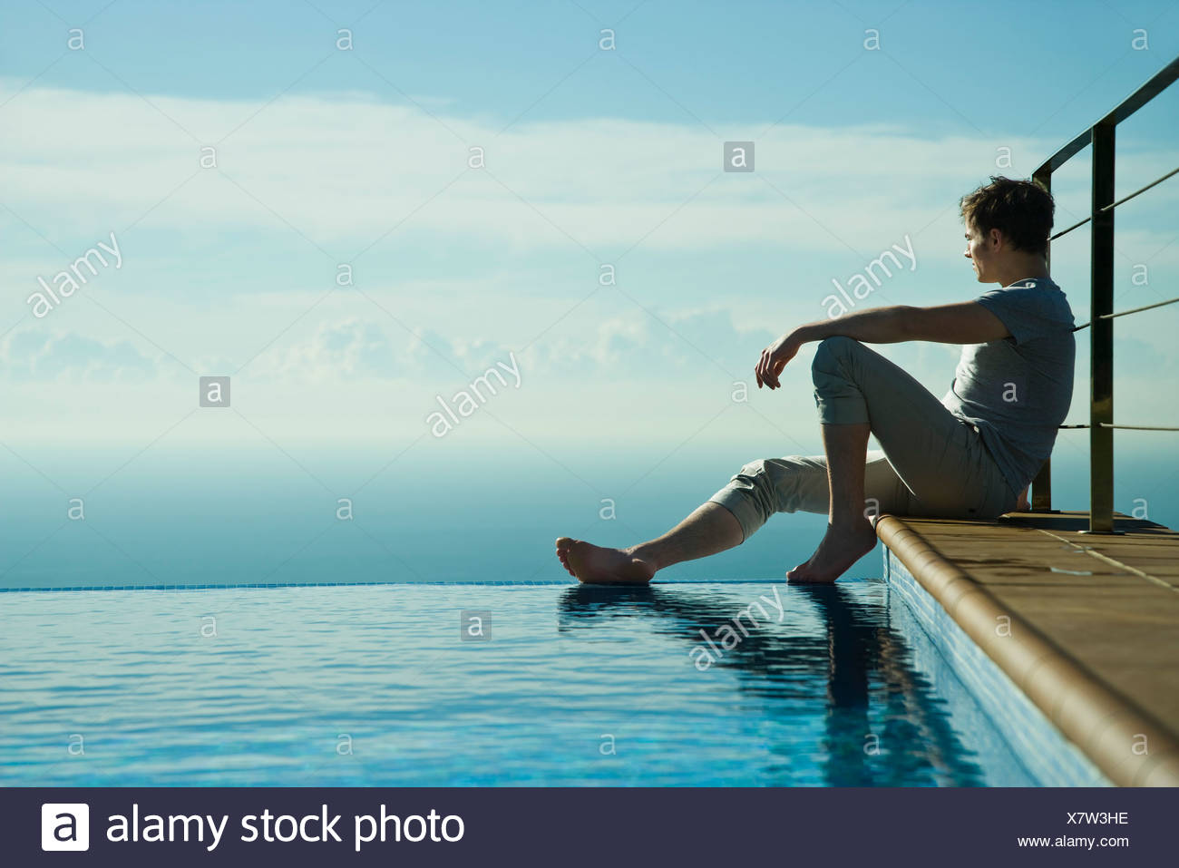 Man sitting on edge of infinity pool, looking at view - Stock Image