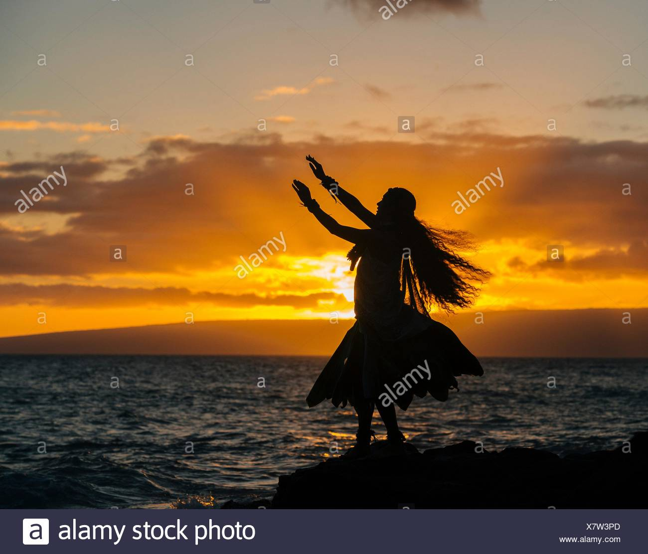 Silhouetted young woman in traditional costume, hula dancing on coastal rock at sunset, Maui, Hawaii, USA - Stock Image