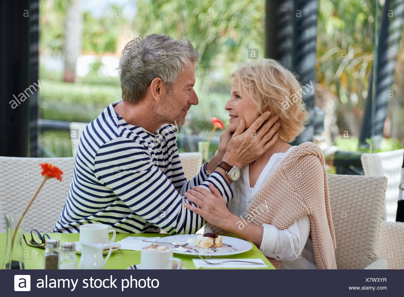 Couple, Best Ager, in the cafe, he tenderly holds her face in his hands were - Stock Image