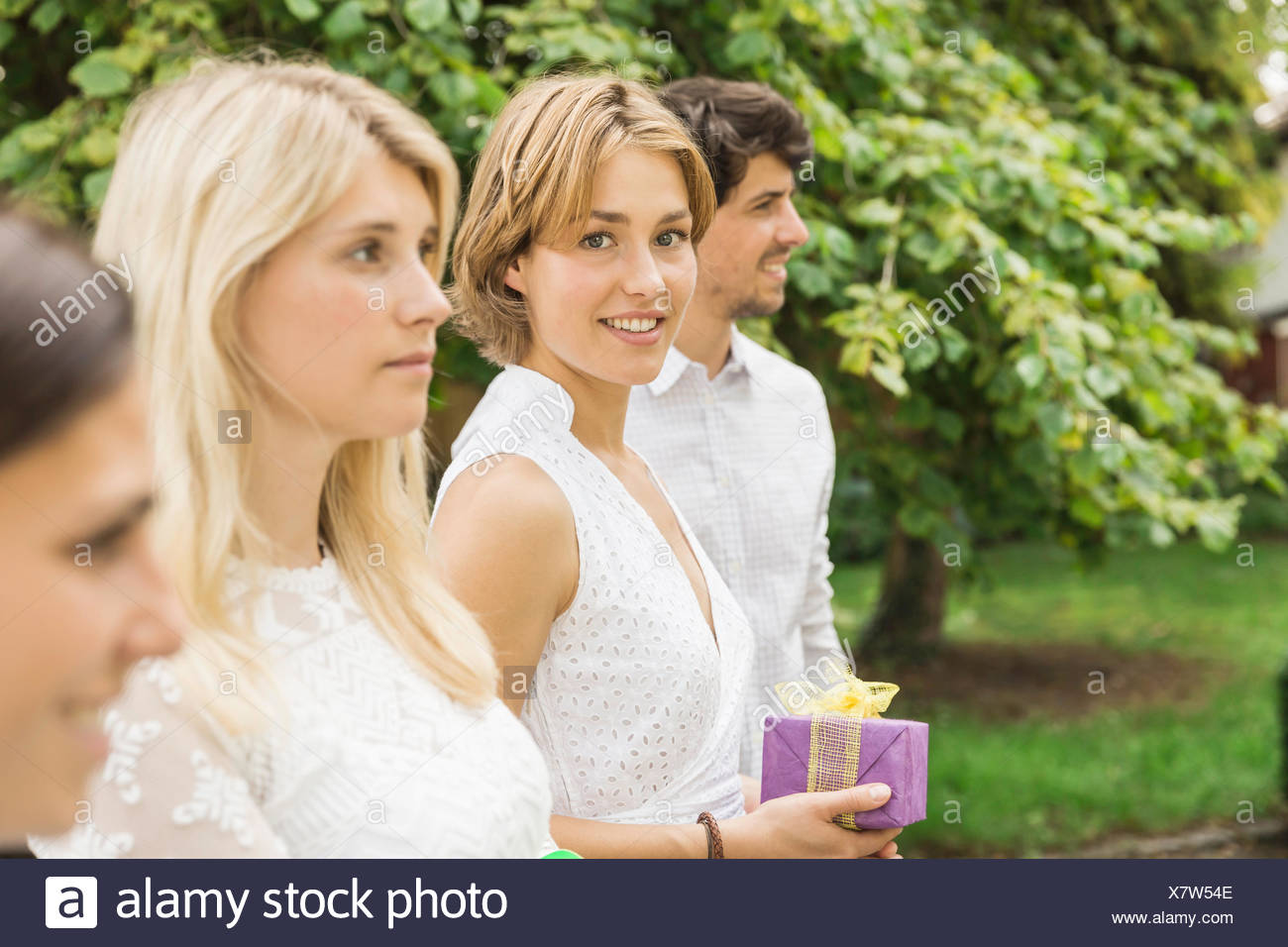 Portrait Of Young Man And Three Women Holding Birthday Gift In Garden