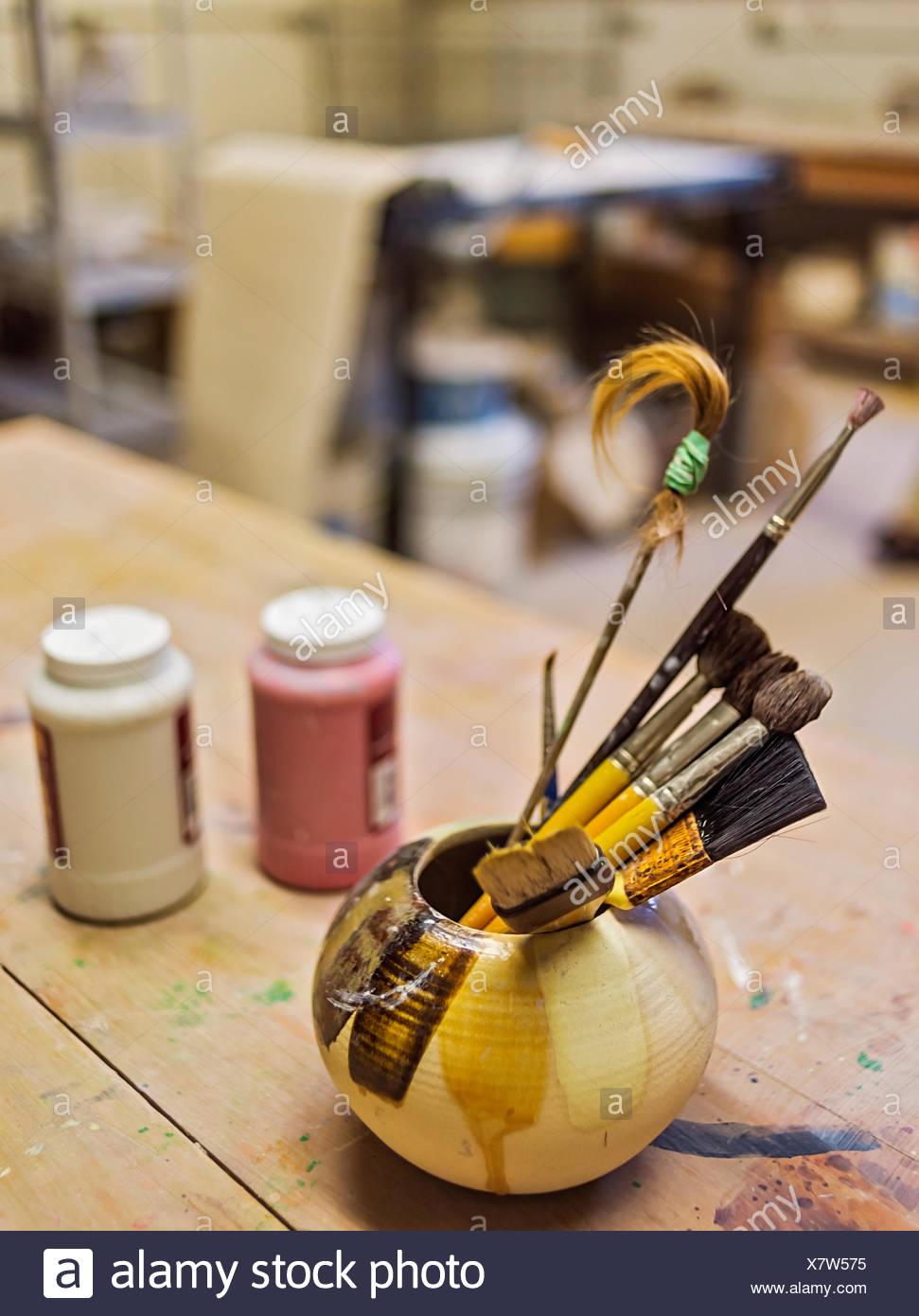Brushes in bowl in art studio Stock Photo