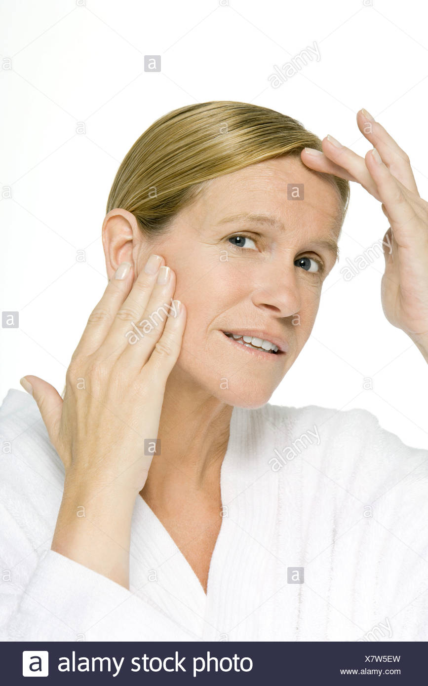 Woman touching forehead and cheek, close-up - Stock Image