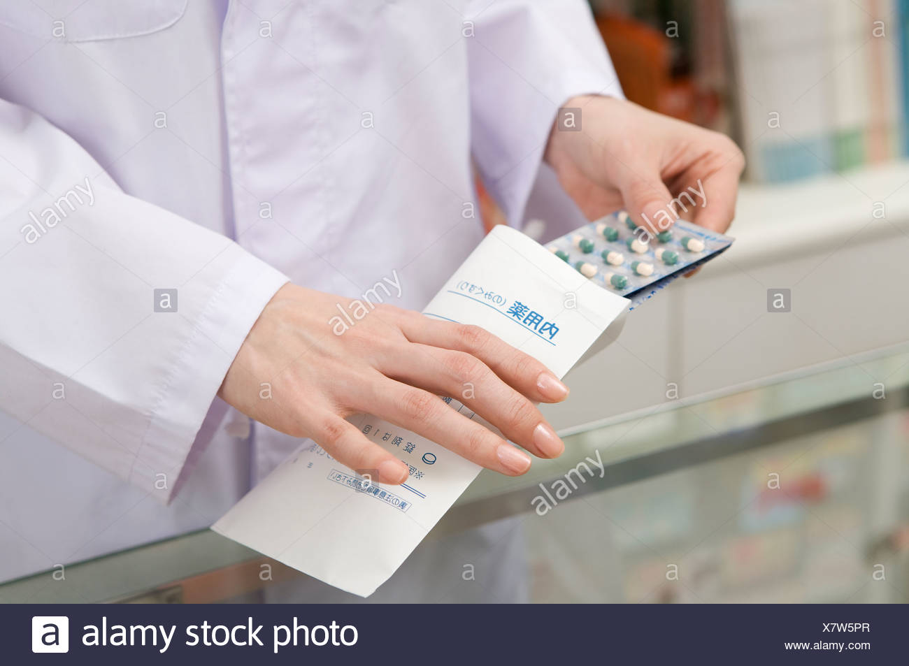 Pharmacist Putting Medicine into Pouch - Stock Image