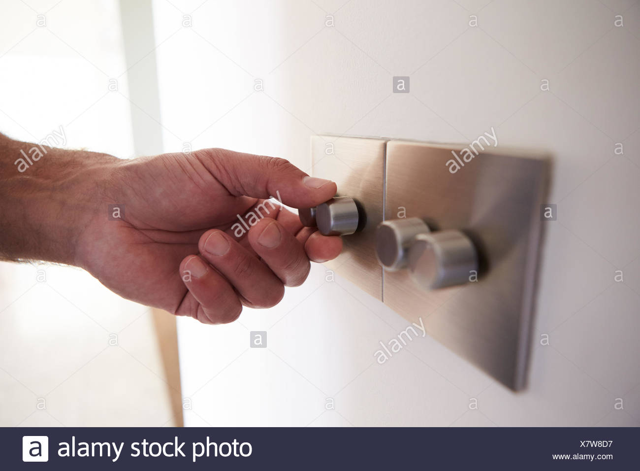 Close Up Shot Of Man Turning Down Electrical Dimmer Switch - Stock Image