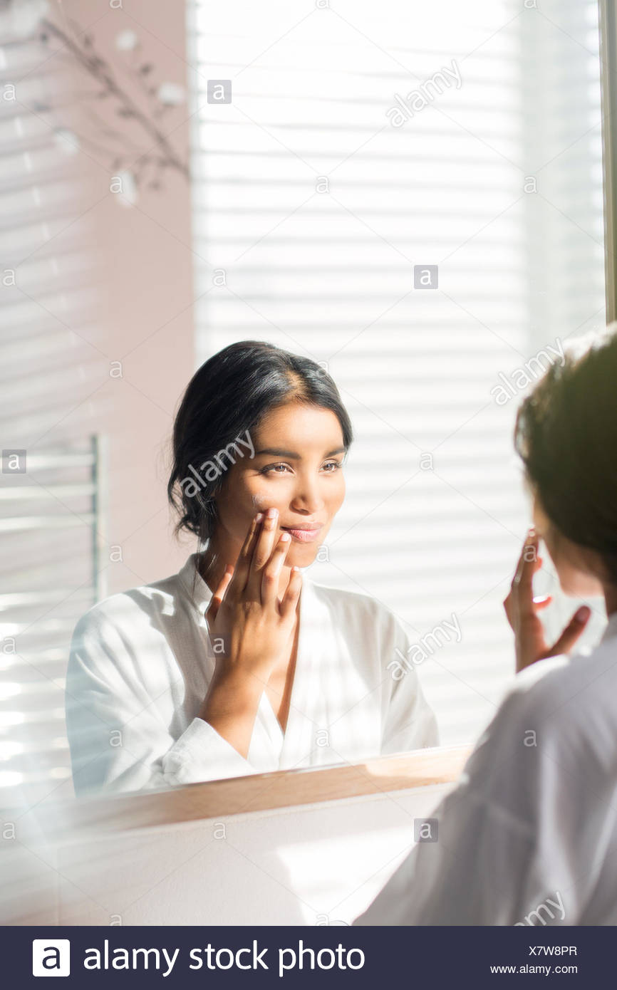 Woman applying moisturizer to face in bathroom mirror - Stock Image