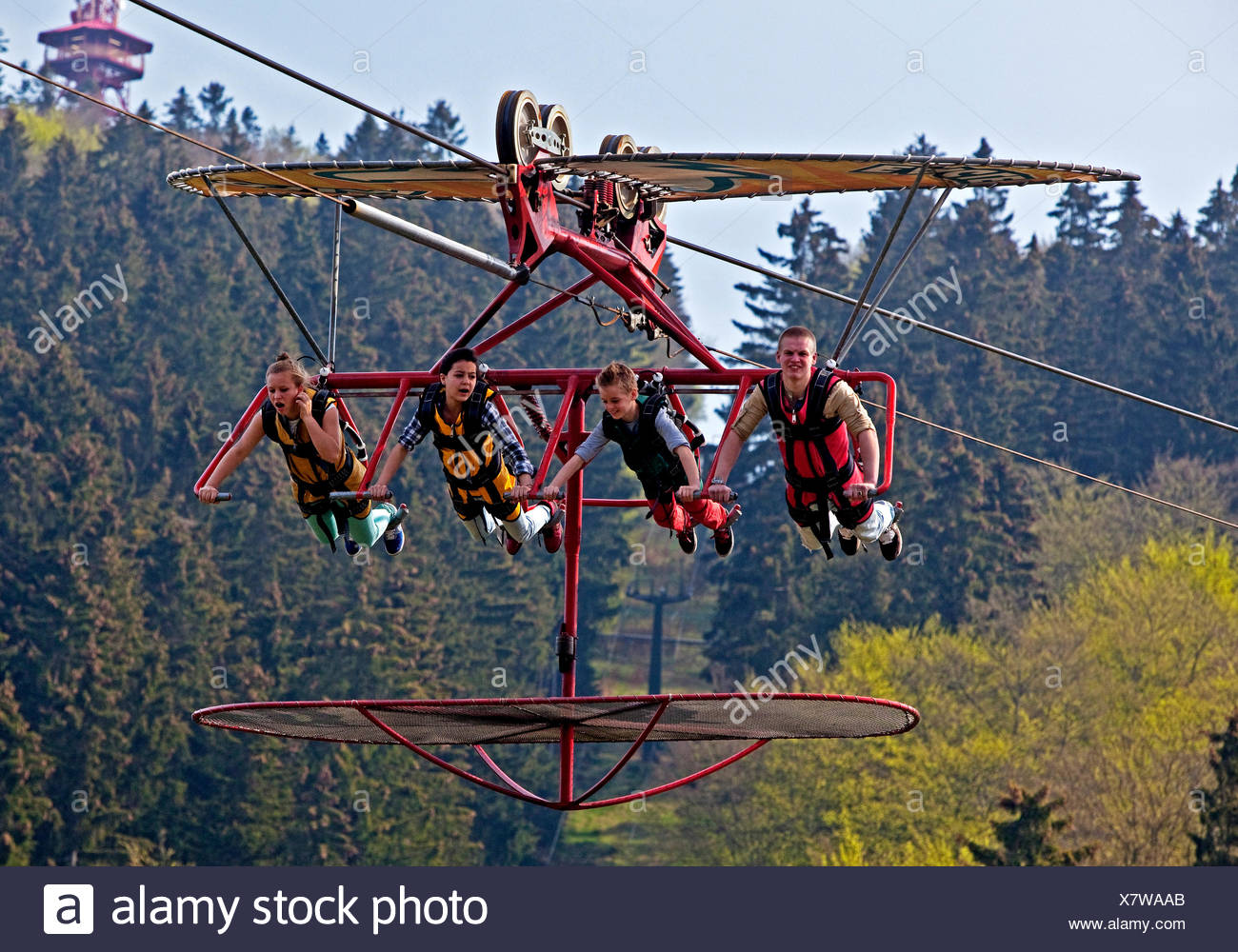 four young people in hang-gliding simulation, Germany, North Rhine-Westphalia, Sauerland, Bestwig - Stock Image