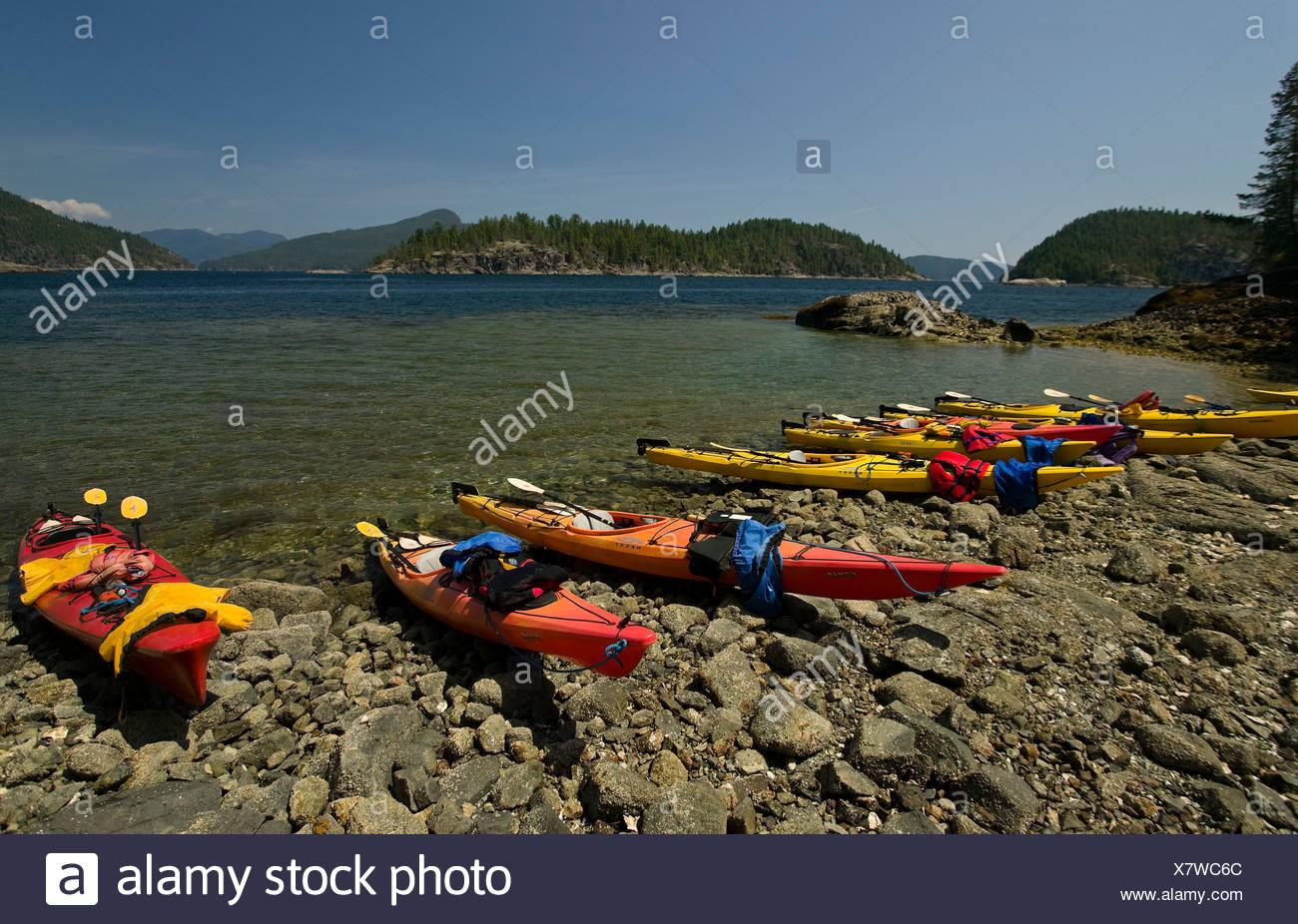 Empty kayaks lie pulled up along the shoreline of Desolation Sound. Desolation Sound, British Columbia, Canada. - Stock Image