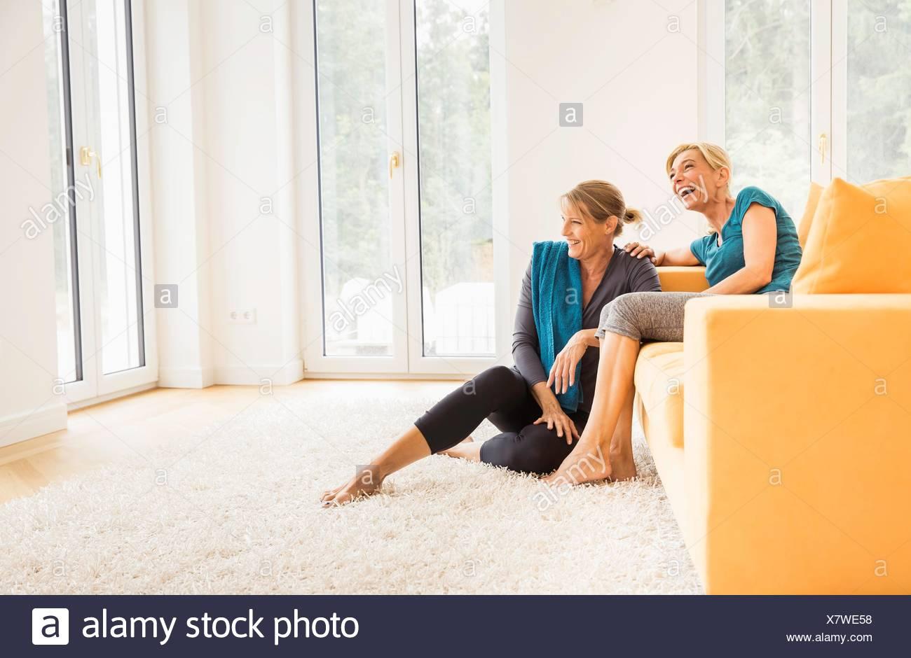 Two mature women taking an exercise break on living room sofa - Stock Image