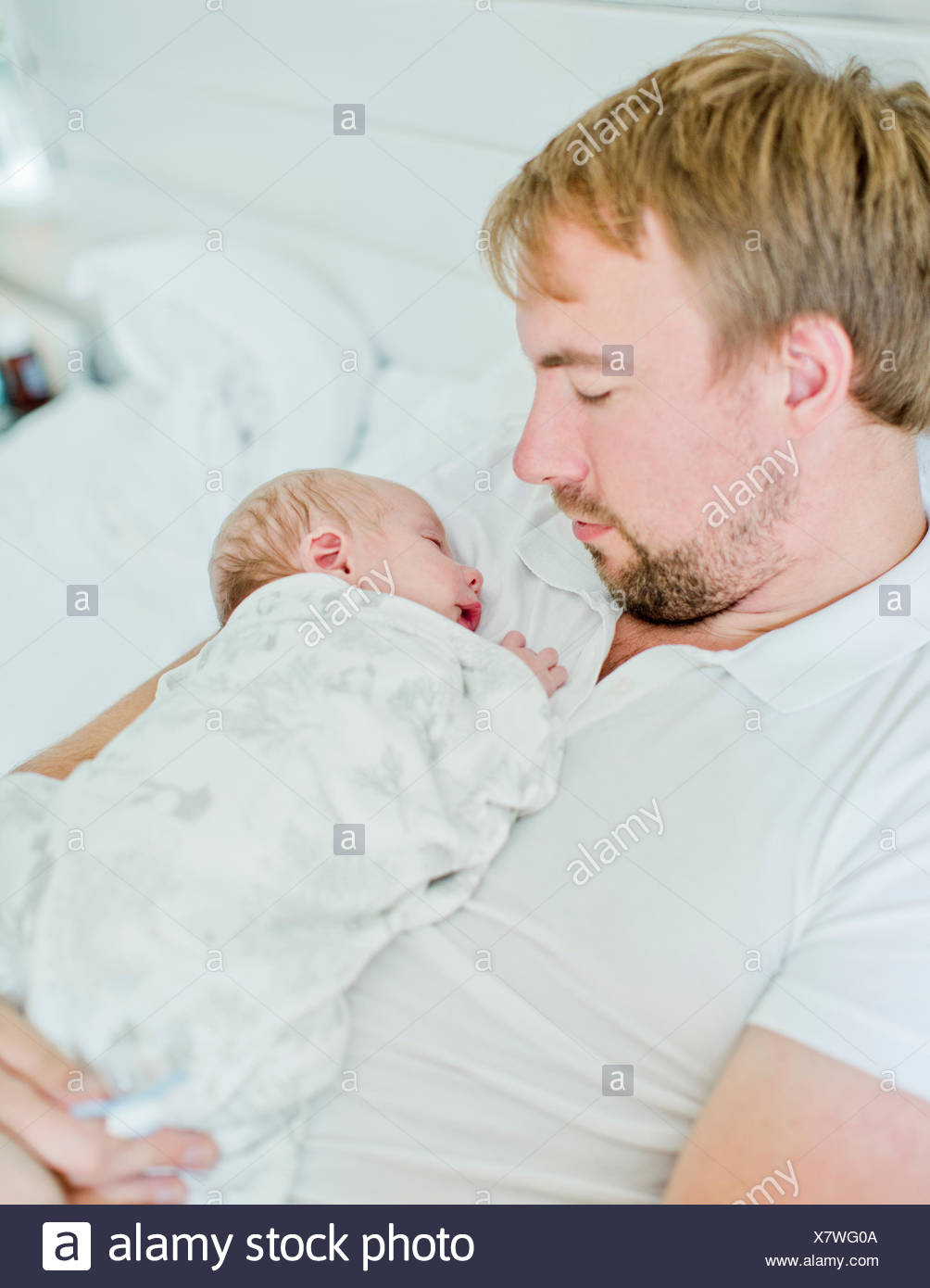 Mid-adult man holding baby boy (0-1 months) in his arms - Stock Image