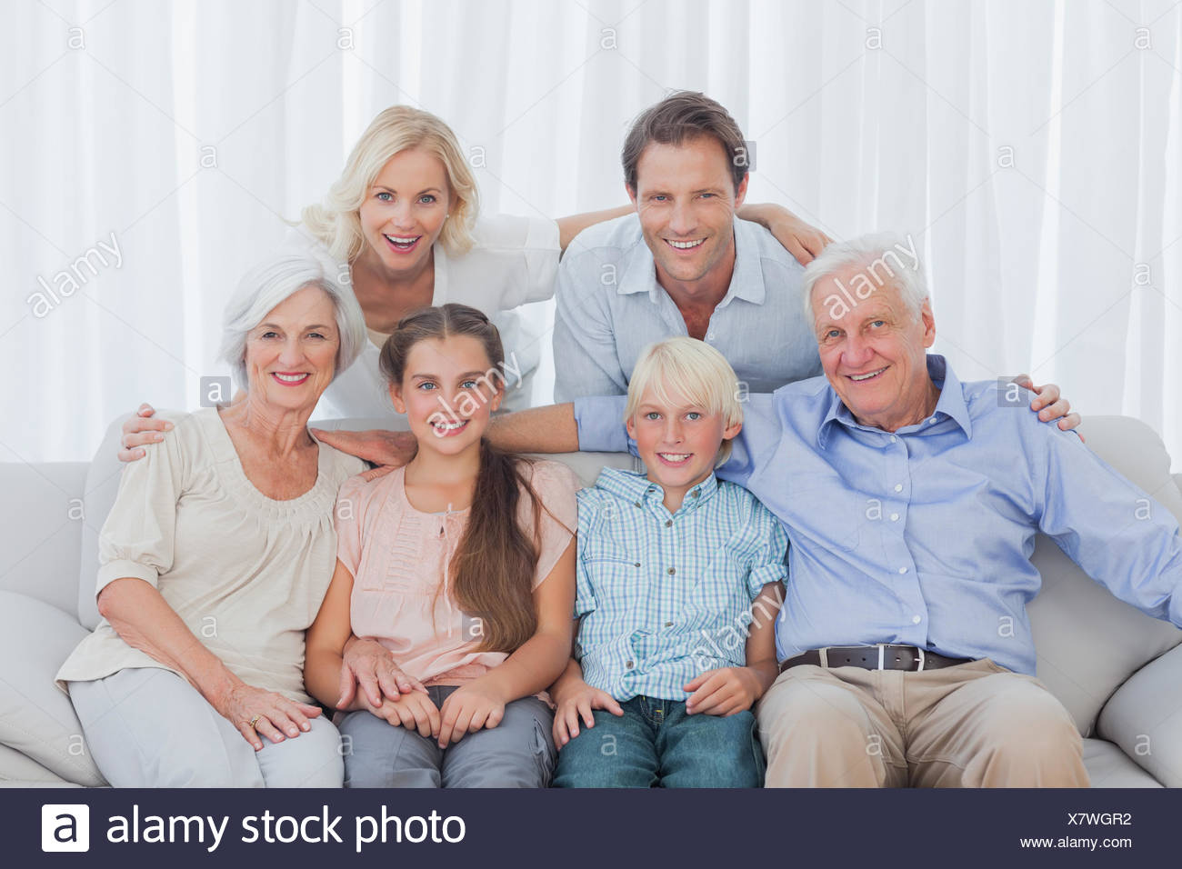 Extended family sitting together on couch - Stock Image