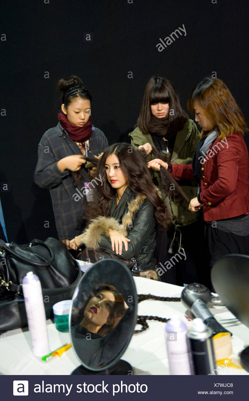 A model gets her hair ready for the Troa Fashion Show. - Stock Image