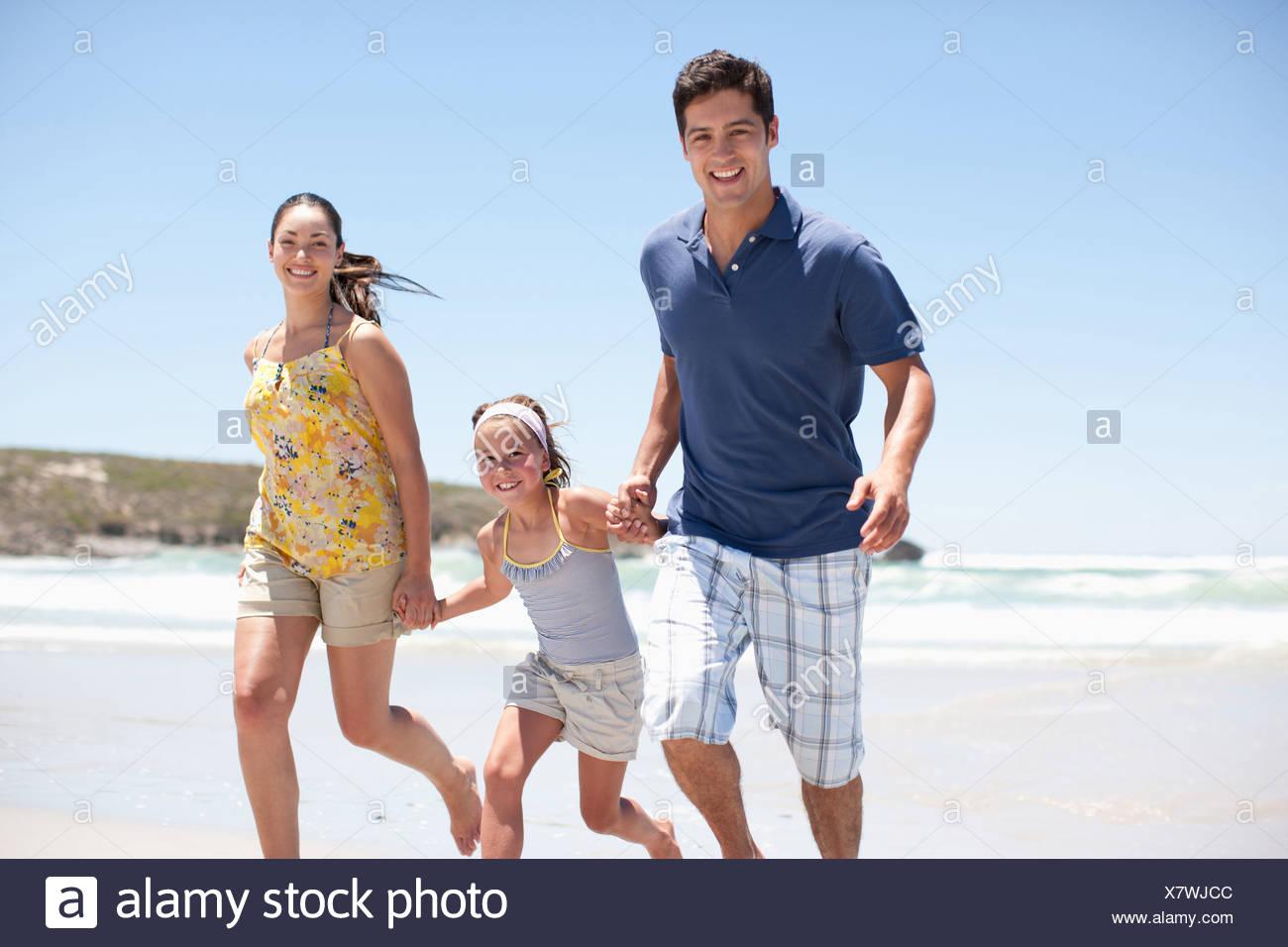 Family running on beach - Stock Image