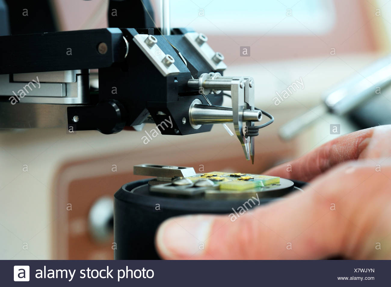Technician adjusting a device to carry out a physical experiment - Stock Image