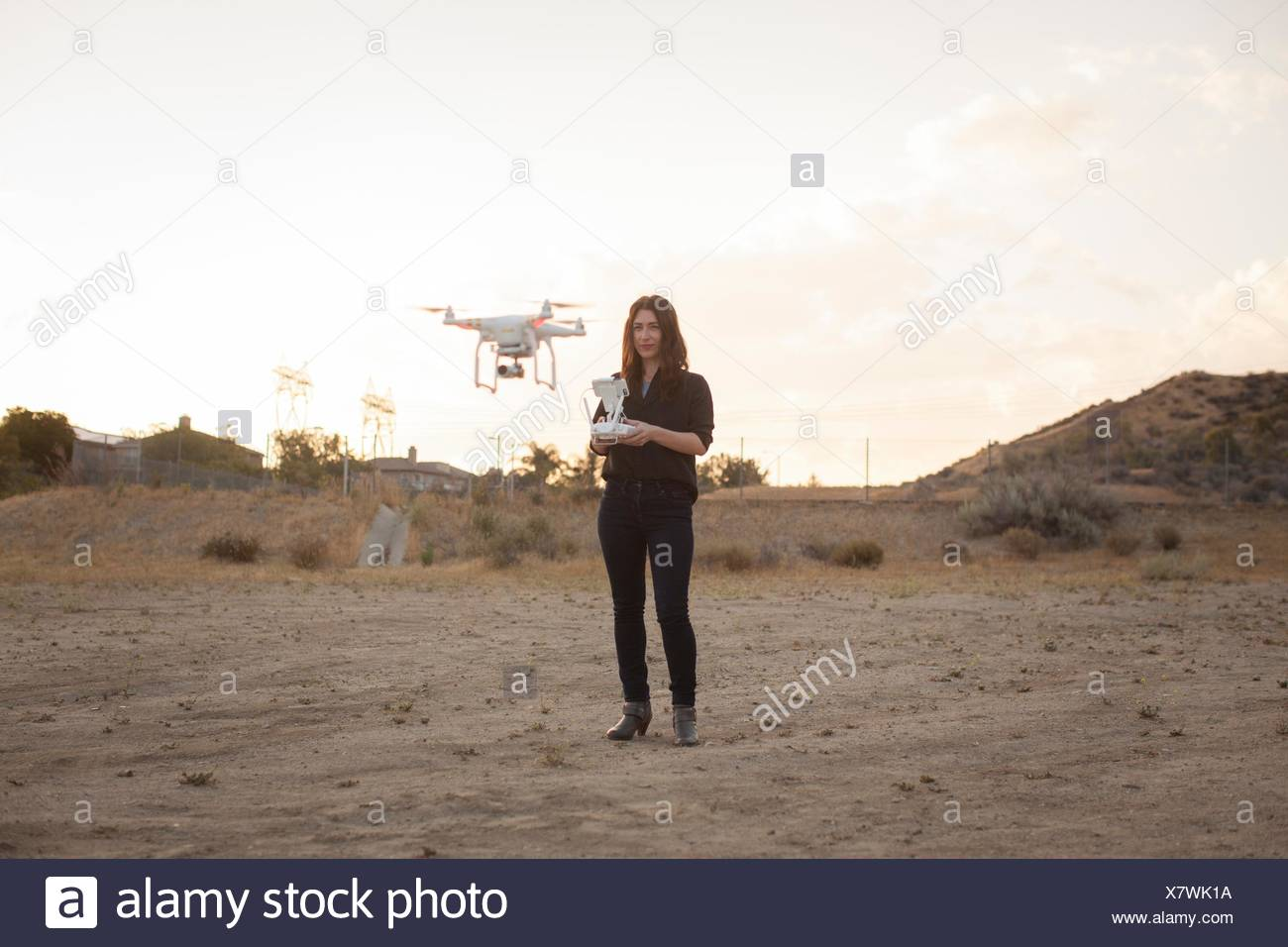 Female commercial operator on scrubland flying drone, Santa Clarita, California, USA Stock Photo