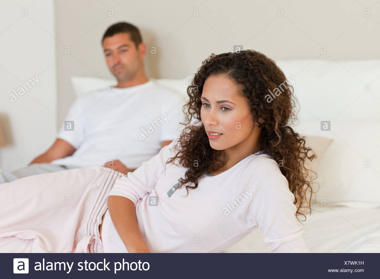Thoughtful woman with her husband on the bed - Stock Image