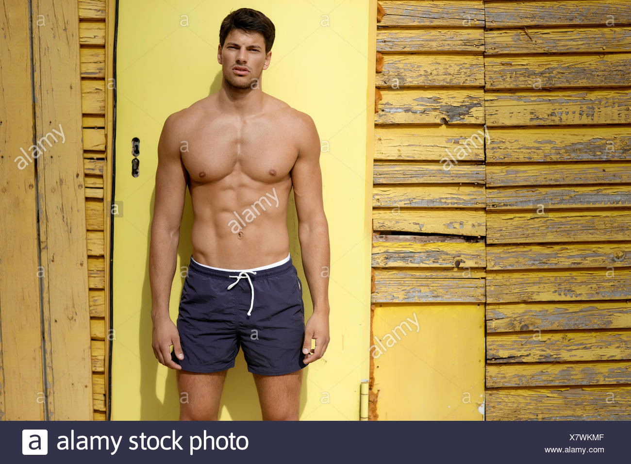 Portrait of athletic young man standing in front of yellow wooden wall - Stock Image