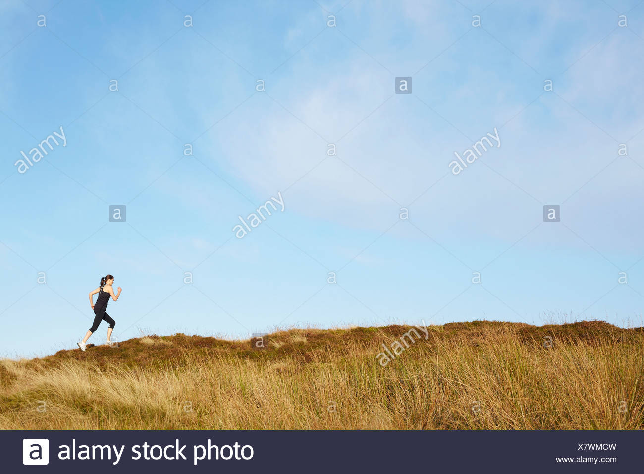 Woman running on rural hillside Stock Photo