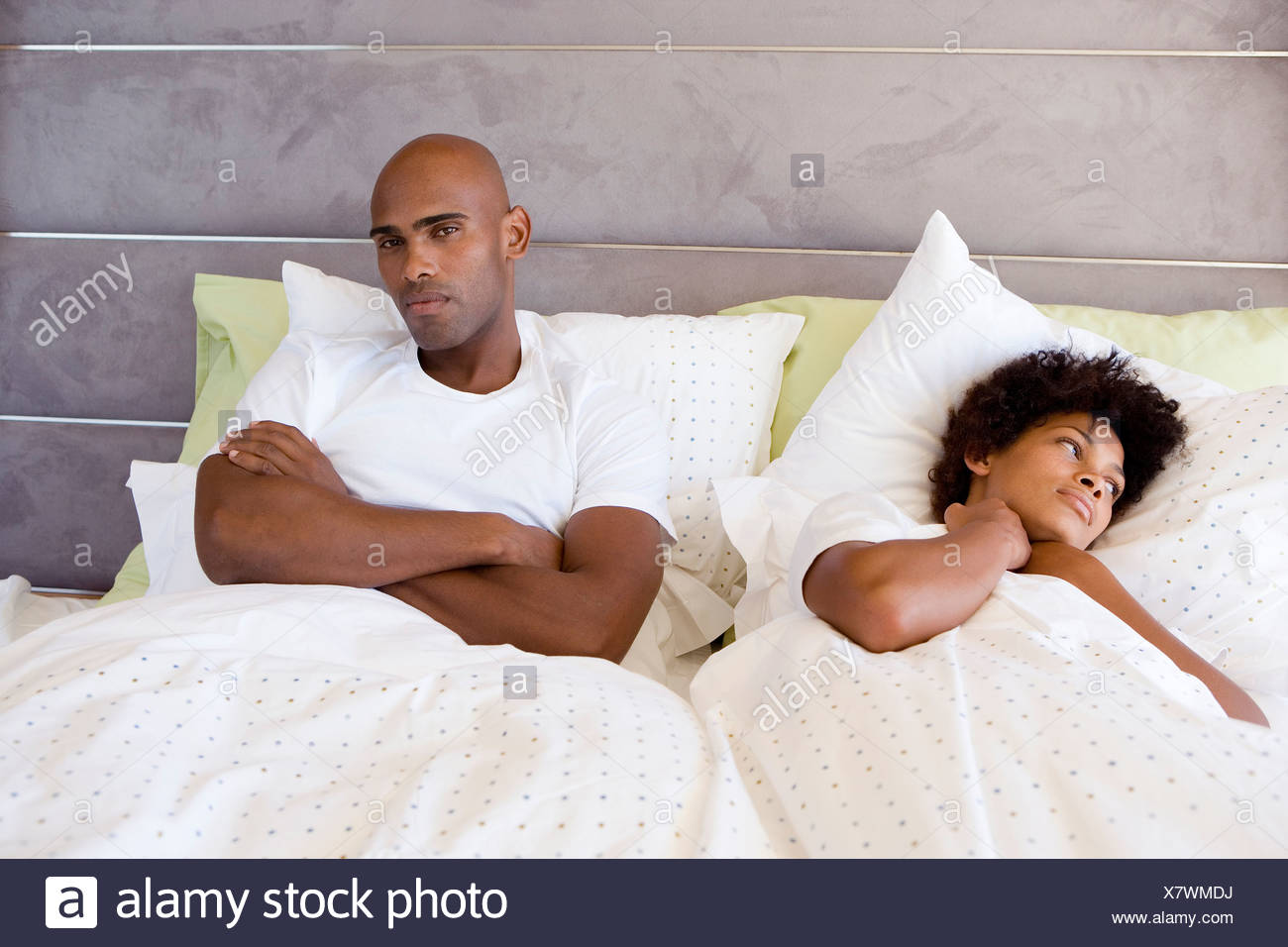 Young couple in bed, man sitting up with arms crossed, portrait - Stock Image