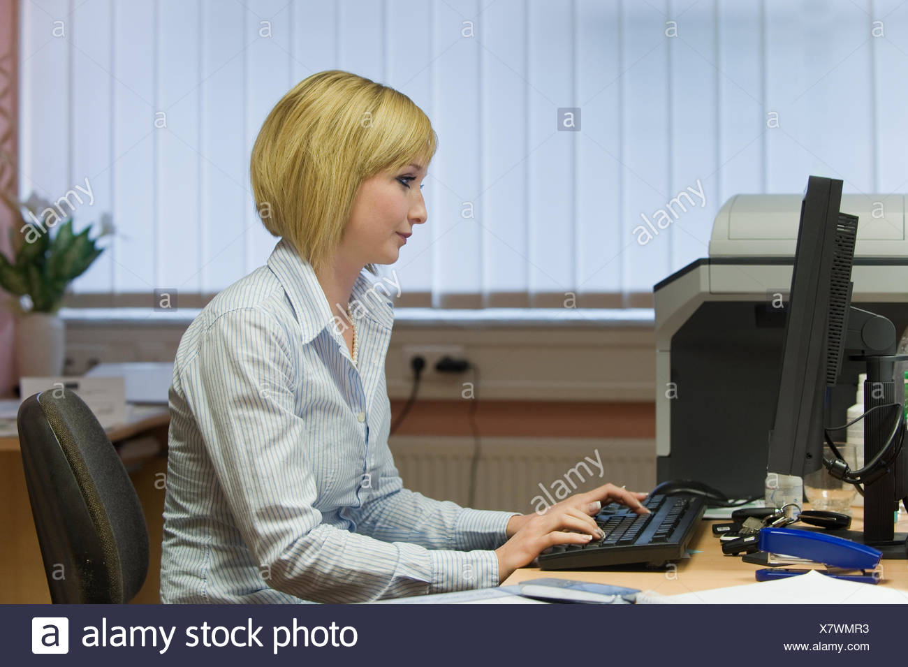 Young blonde secretary working on computer - Stock Image