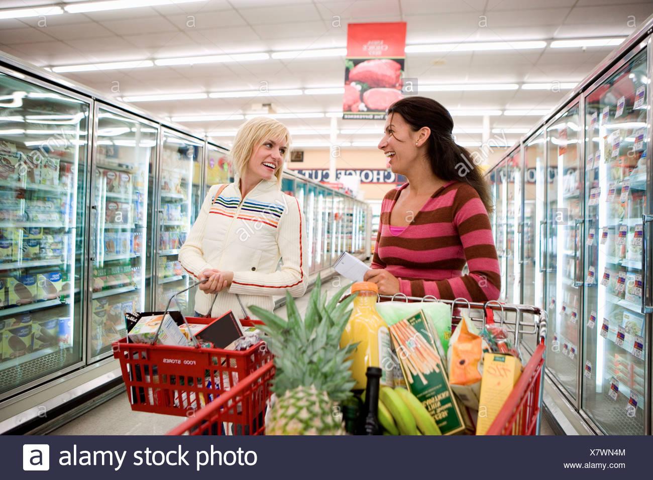Two women shopping in supermarket standing beside trolleys