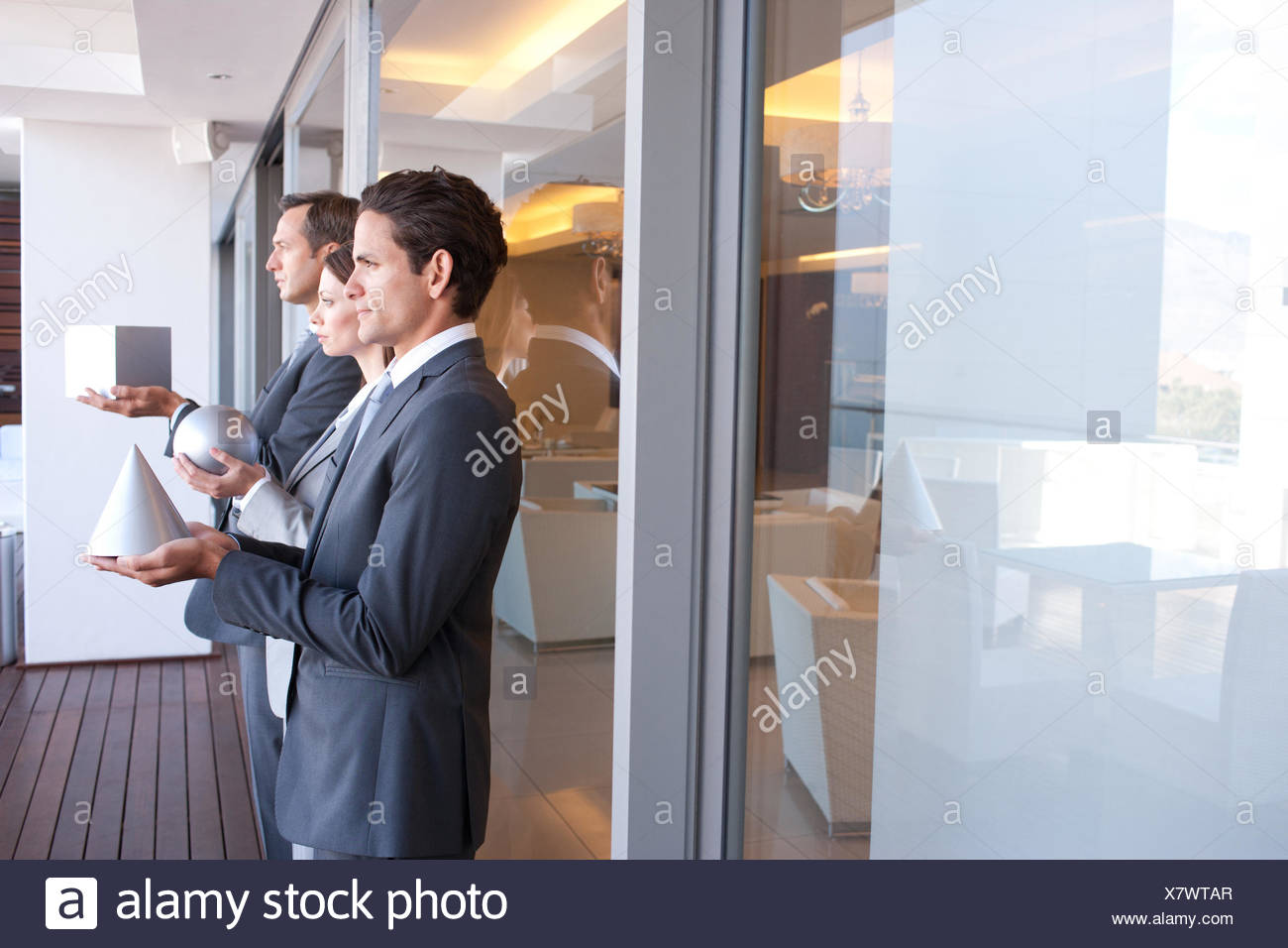 Business people holding geometric shapes - Stock Image