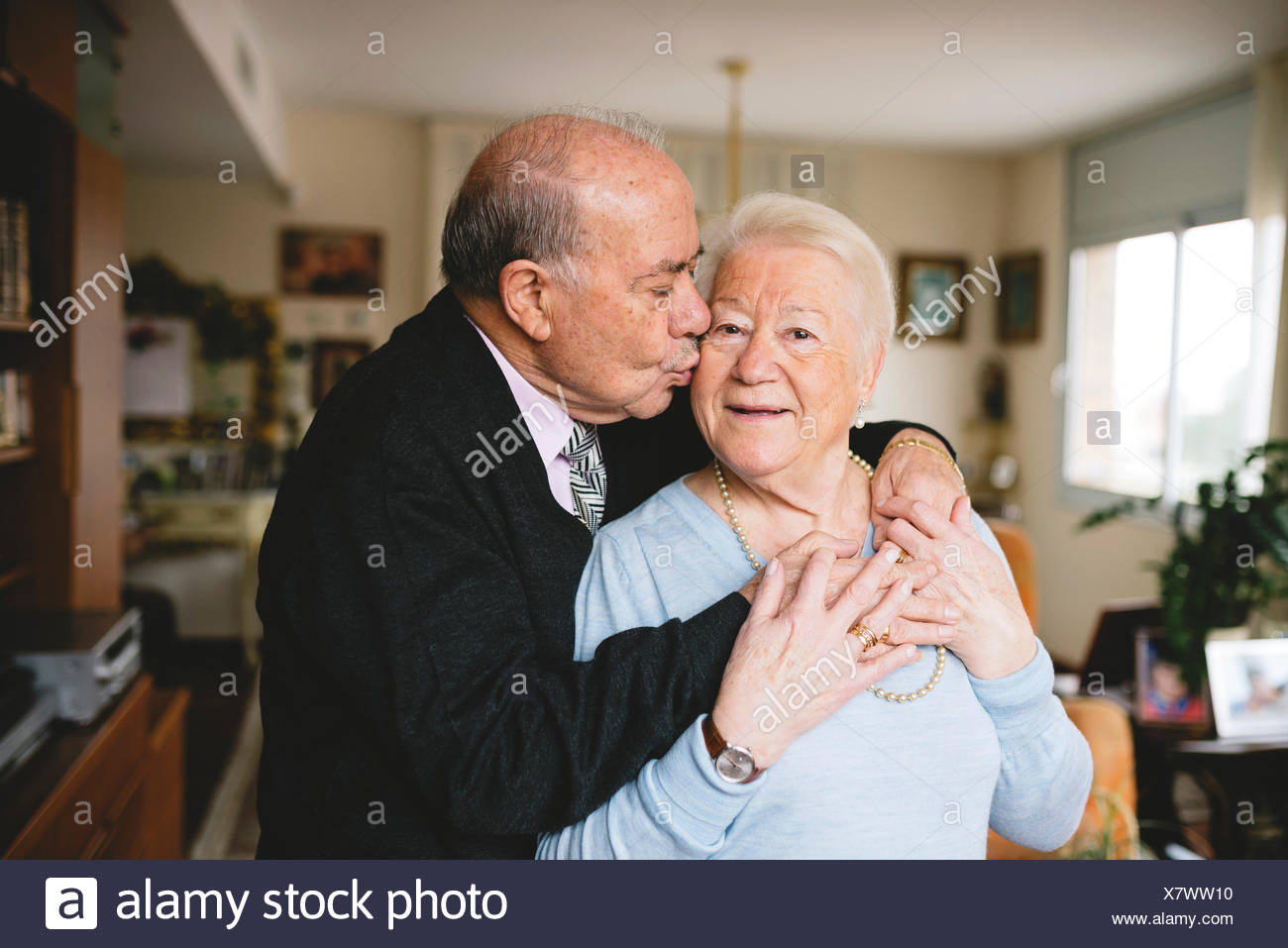 Senior couple hugging and kissing at home Stock Photo