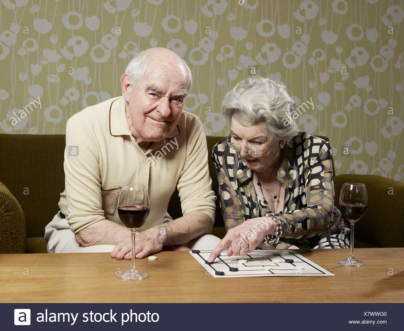 Senior man grimaces as senior woman contemplates a move playing muehle - Stock Image