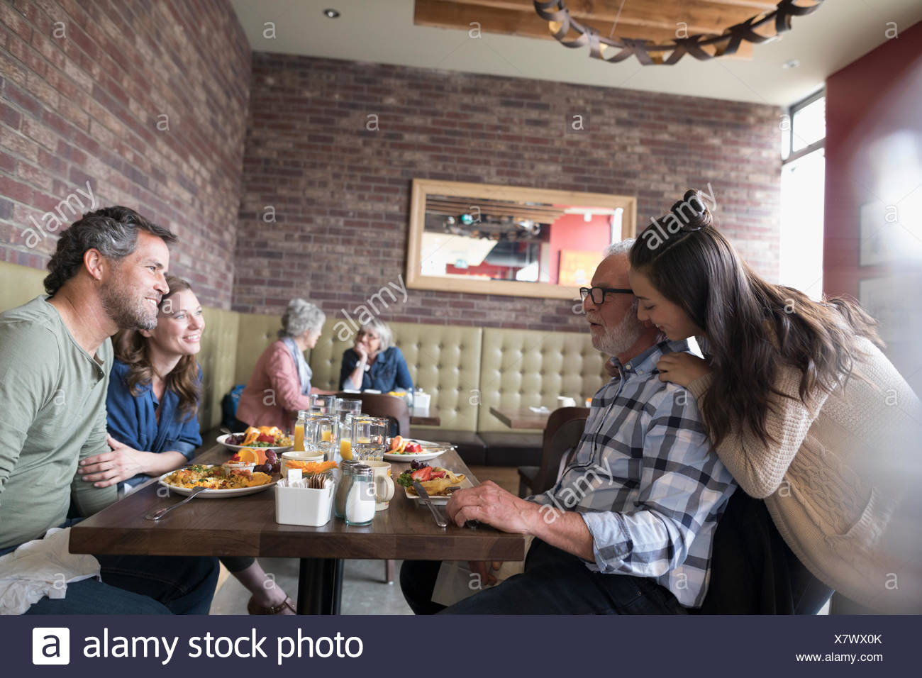 Affectionate granddaughter hugging grandfather, dining at diner table - Stock Image