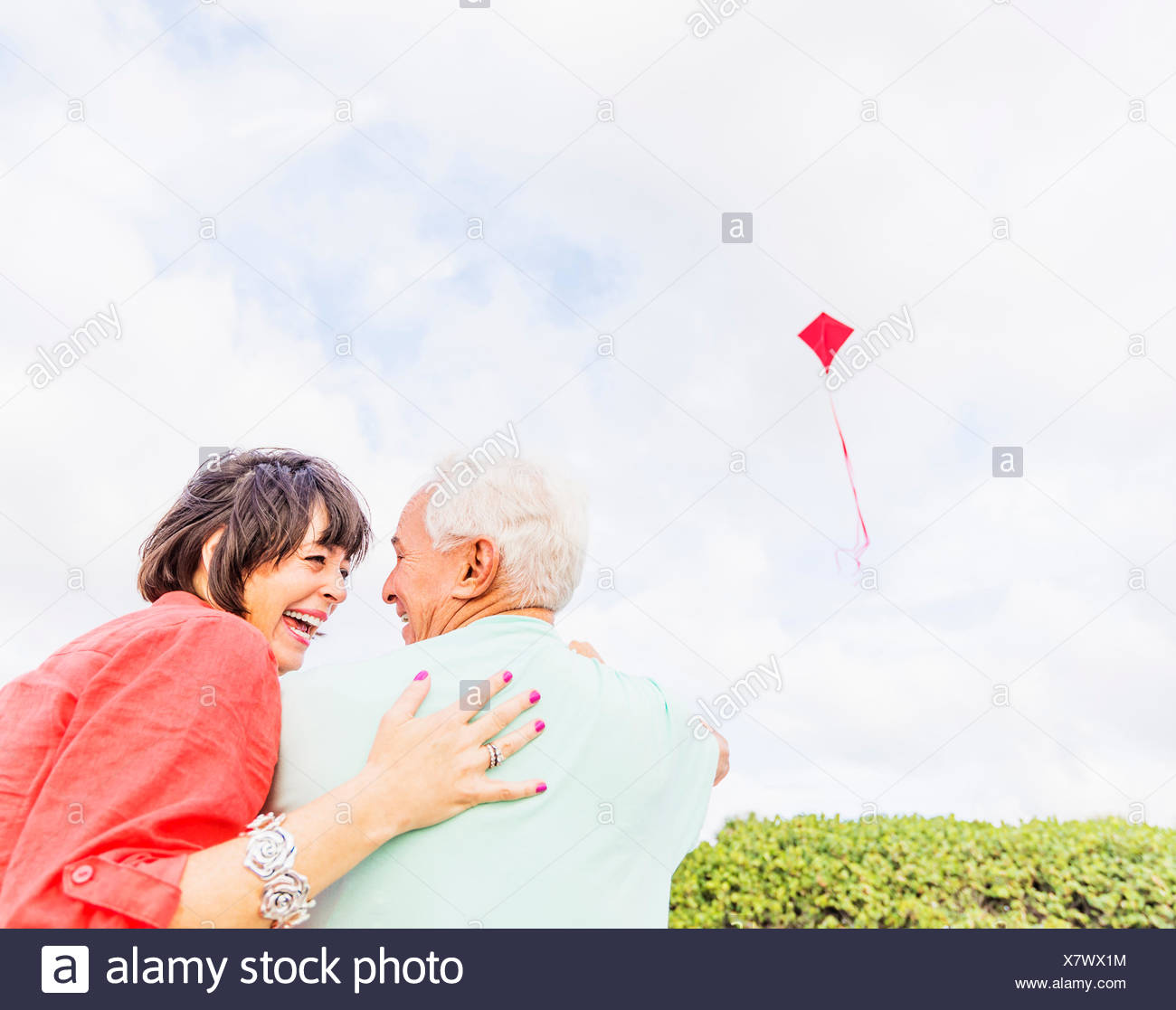 Low-angle view of couple flying kite together Stock Photo