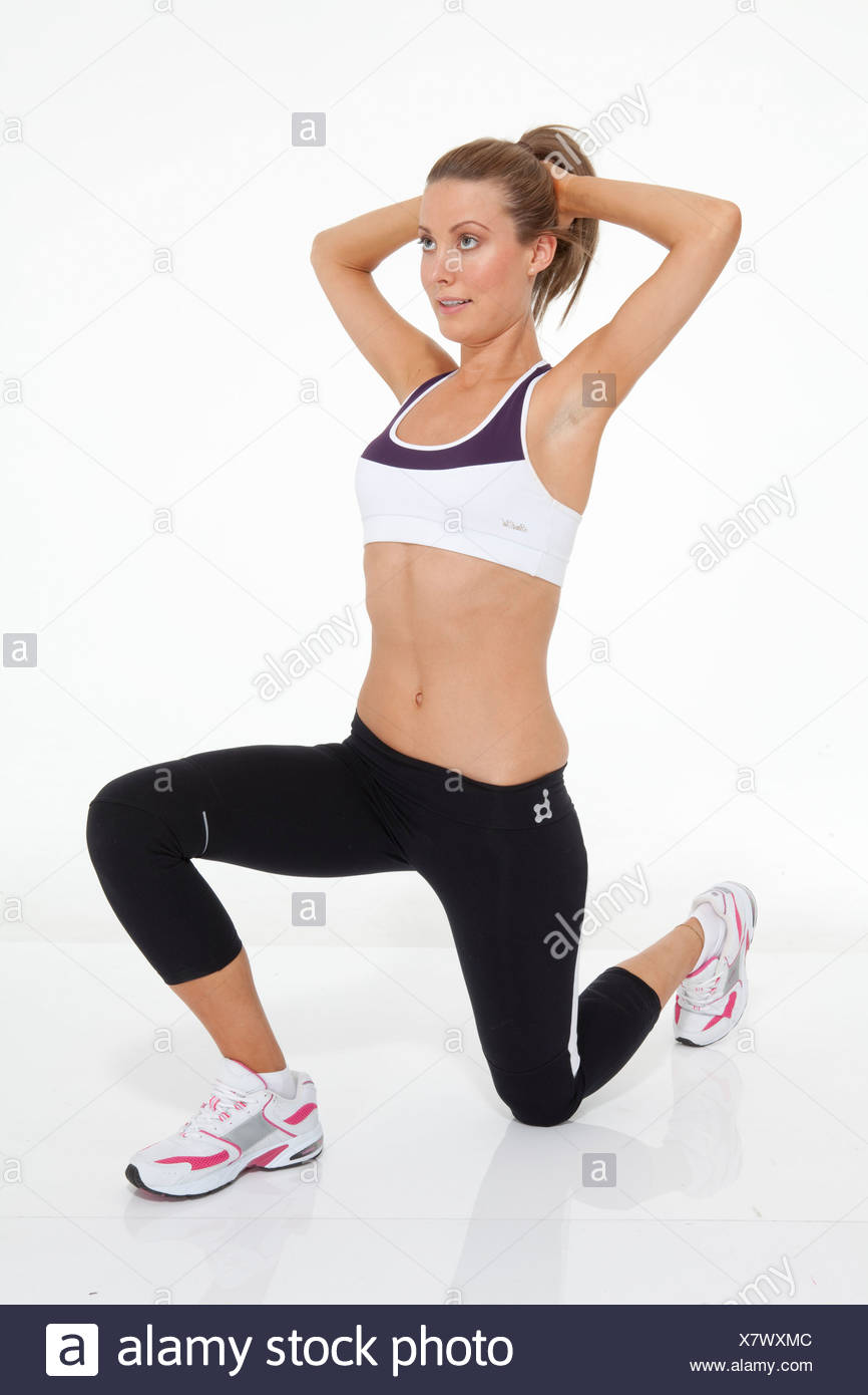Lower body exercise Female fair hair tied into ponytail, wearing a cropped vest, black leggings and trainers, performing a - Stock Image