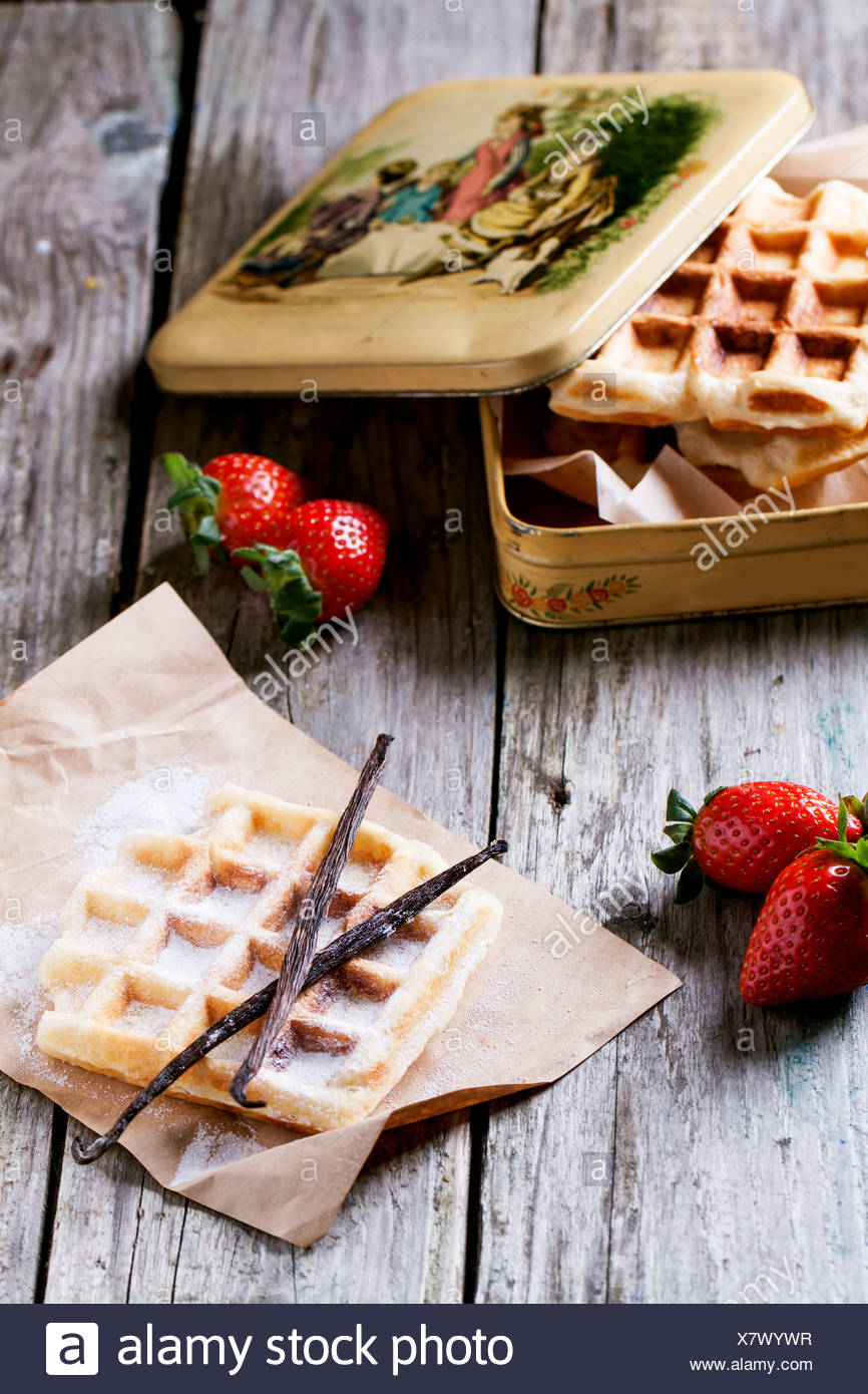 Fresh waffles with vanilla sticks and strawberries served with vintage metal box over old wooden table - Stock Image
