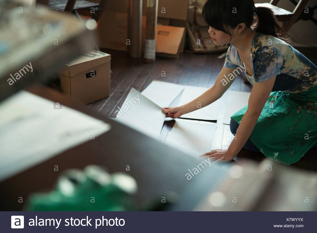 Female designer reviewing prints on the floor - Stock Image