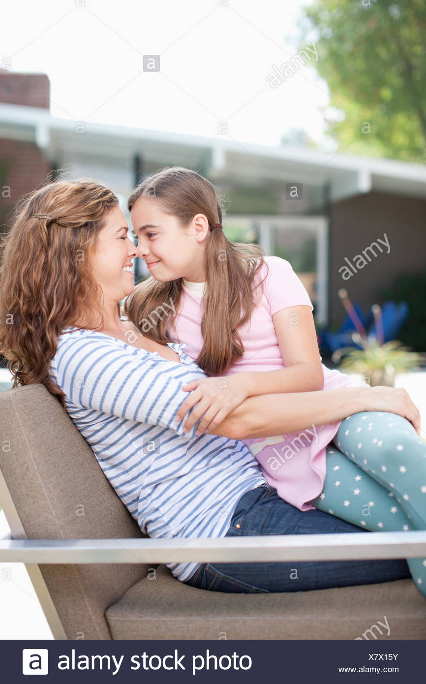Mother and daughter touching noses outdoors - Stock Image