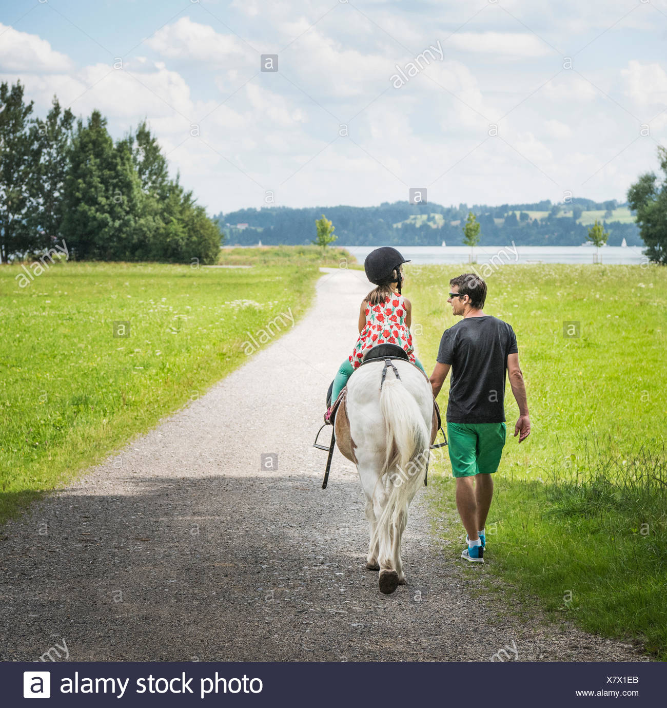 Rear view of father guiding daughter riding horse, Fuessen, Bavaria, Germany Stock Photo