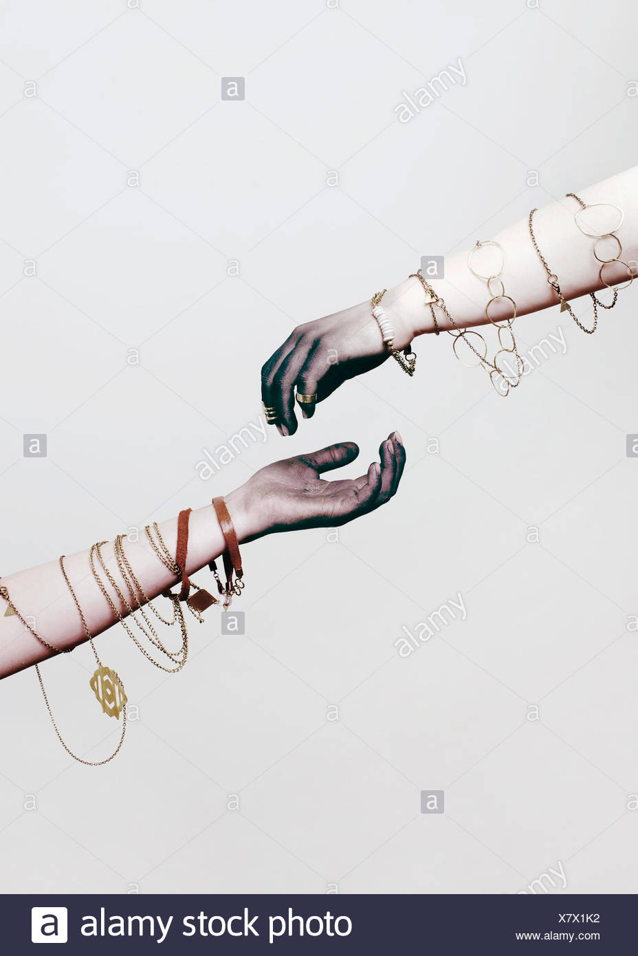 Two arms with jewelry wrapped around them - Stock Image