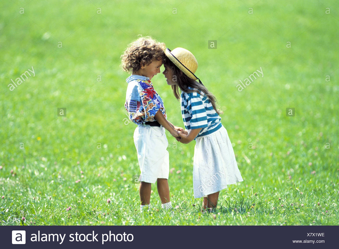 Meadow, girl, boy, hands hold, eye contact, outside, children, two, comradeship, affection, friends, friendship, 'the first love', falls in love, flirtation, flirt, - Stock Image