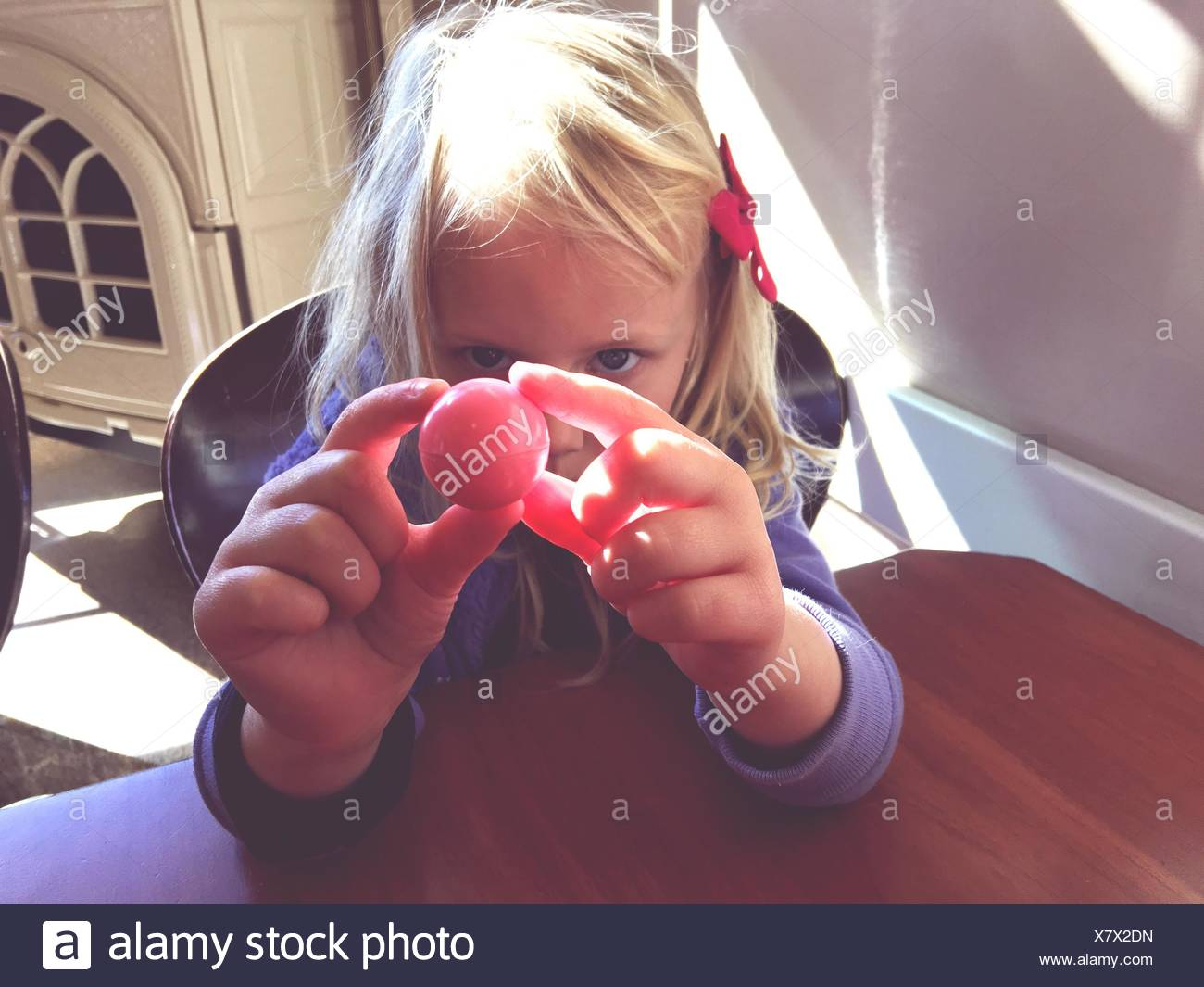 Close-Up Of Blond Girl With Ball At Home - Stock Image