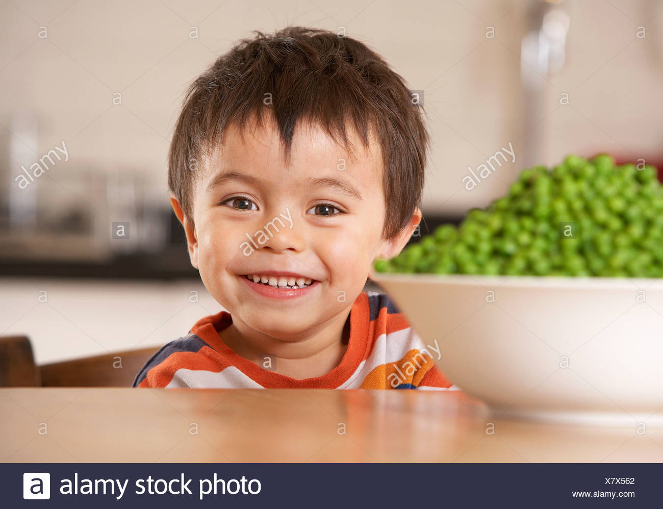 Young boy in kitchen with a bowl of green peas smiling - Stock Image