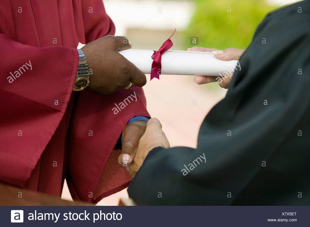 Graduate Receiving Diploma and Handshake, mid section - Stock Image