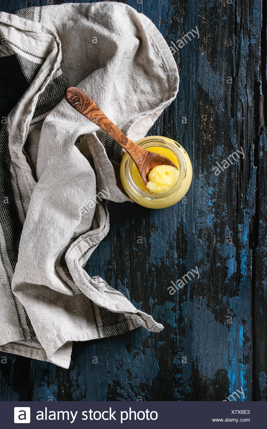 Glass of drawn ghee butter standing with wood spoon and linen textile over old dark blue wooden background. Healthy eating. Top view, copy space - Stock Image