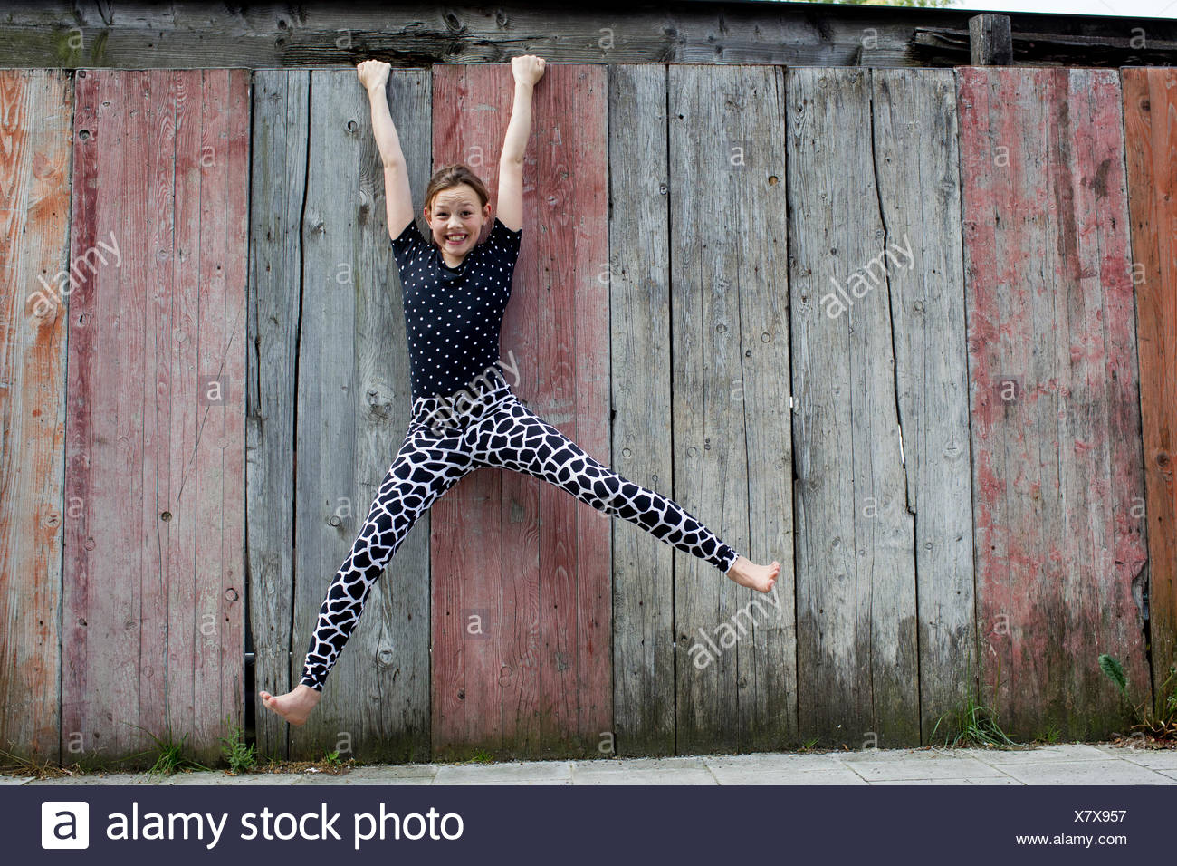 Teenage girl hanging from wooden fence - Stock Image