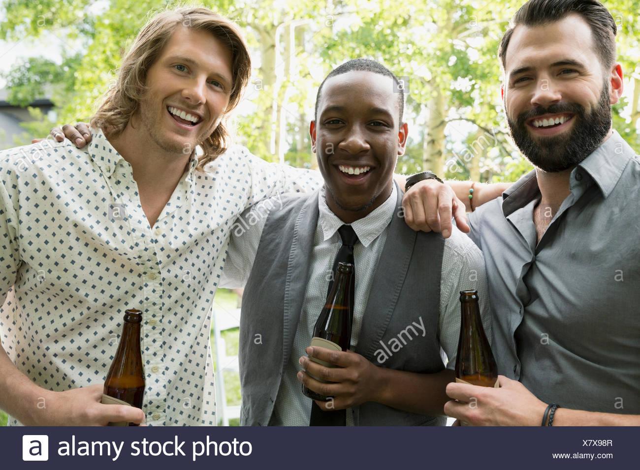 Portrait smiling men drinking beer - Stock Image