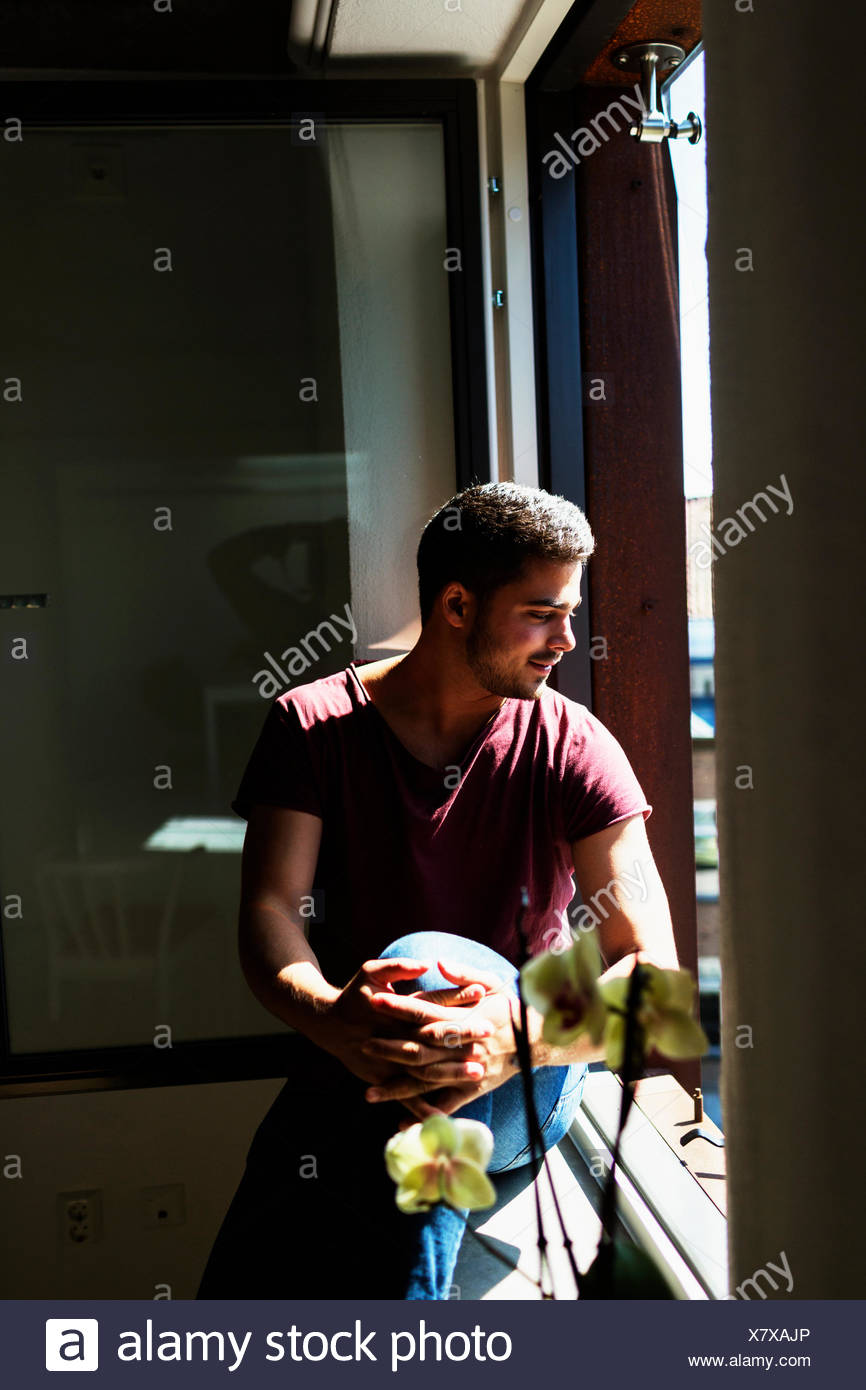 Thoughtful young man sitting on window sill - Stock Image