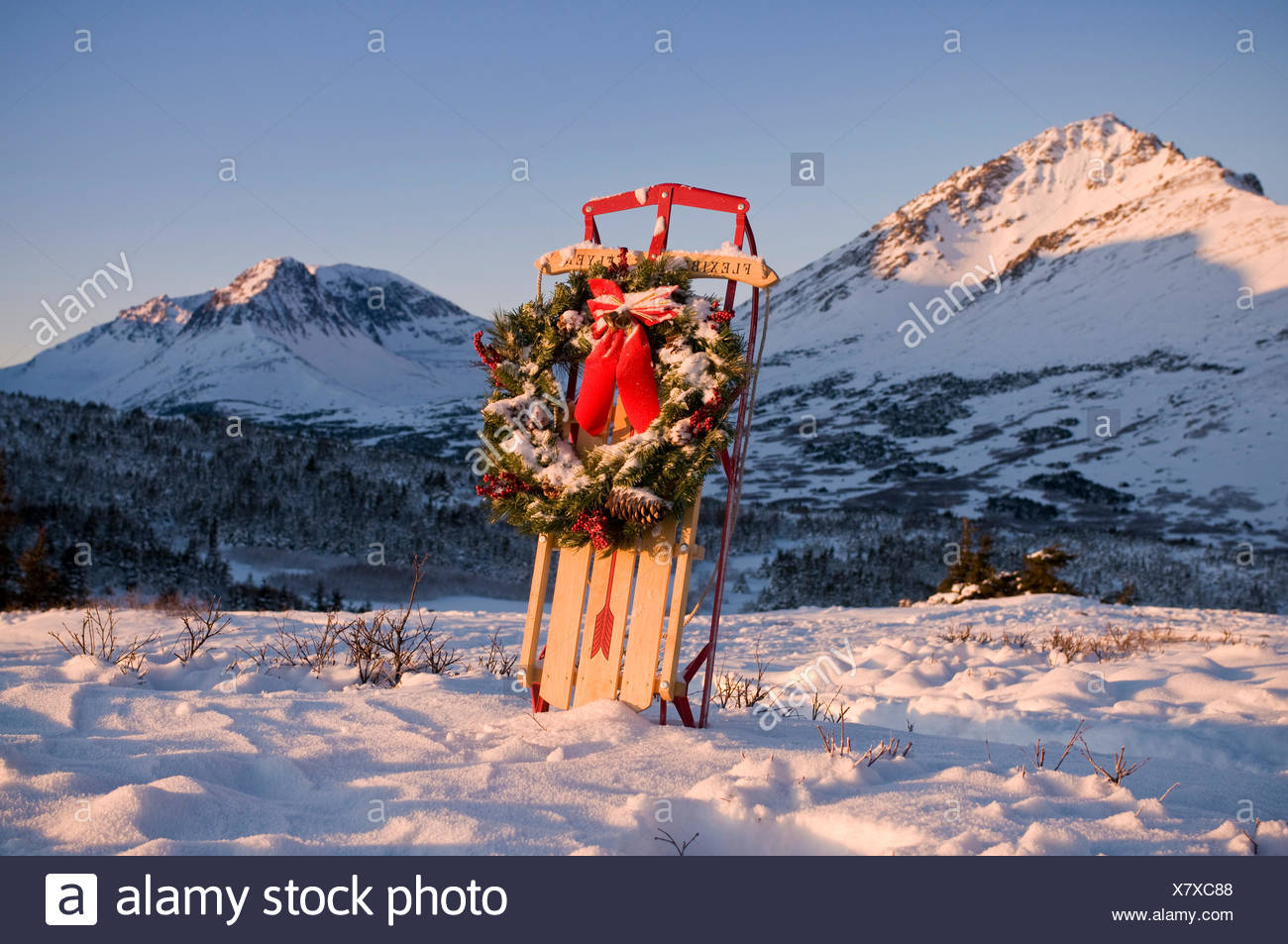 Christmas Wreath Hangs On A Flexible Flyer Sled Propped In A Snowbank In Chugach State Park, Alaska Stock Photo