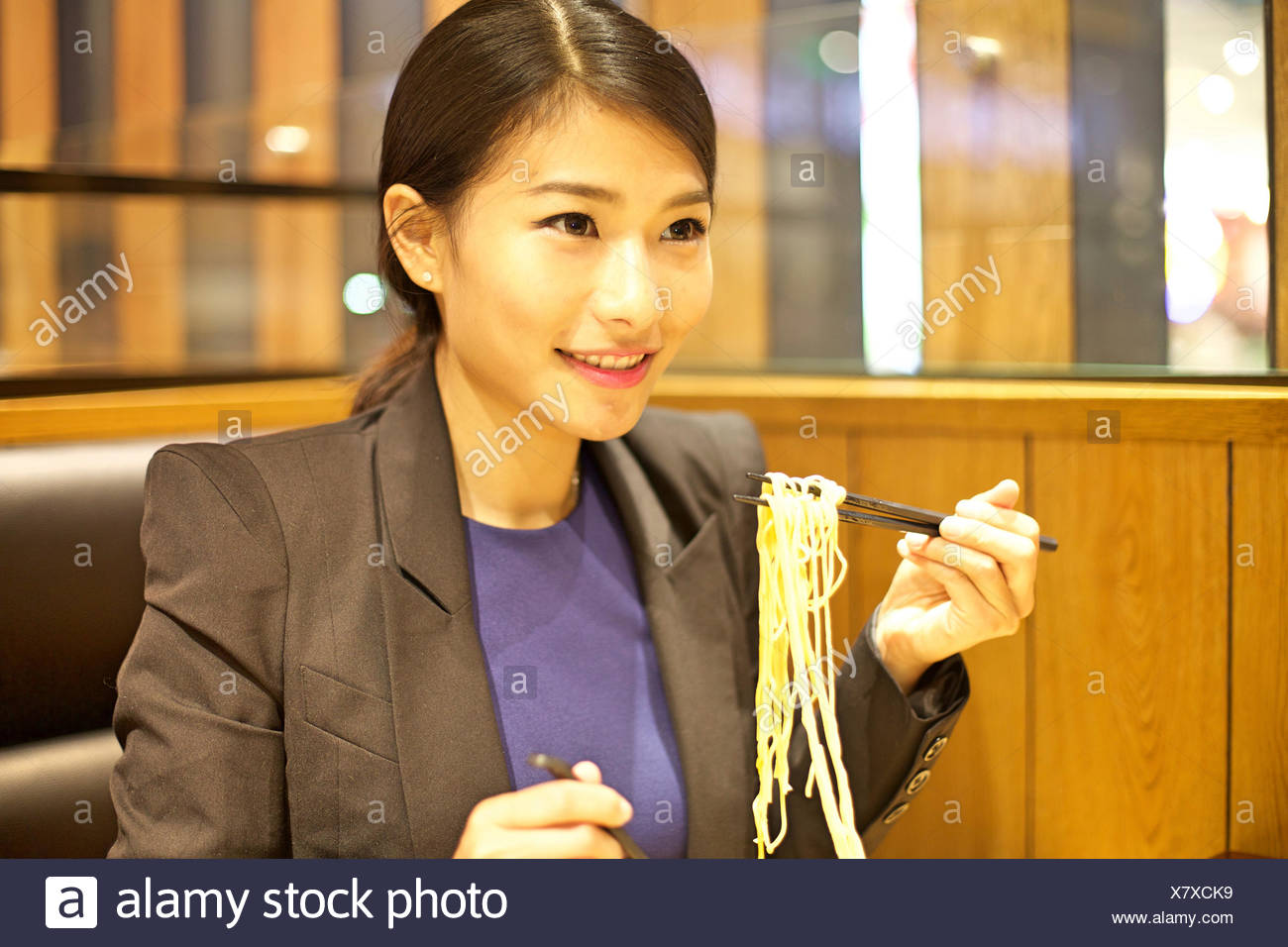 Chinese Woman eating noodles in restaurant - Stock Image